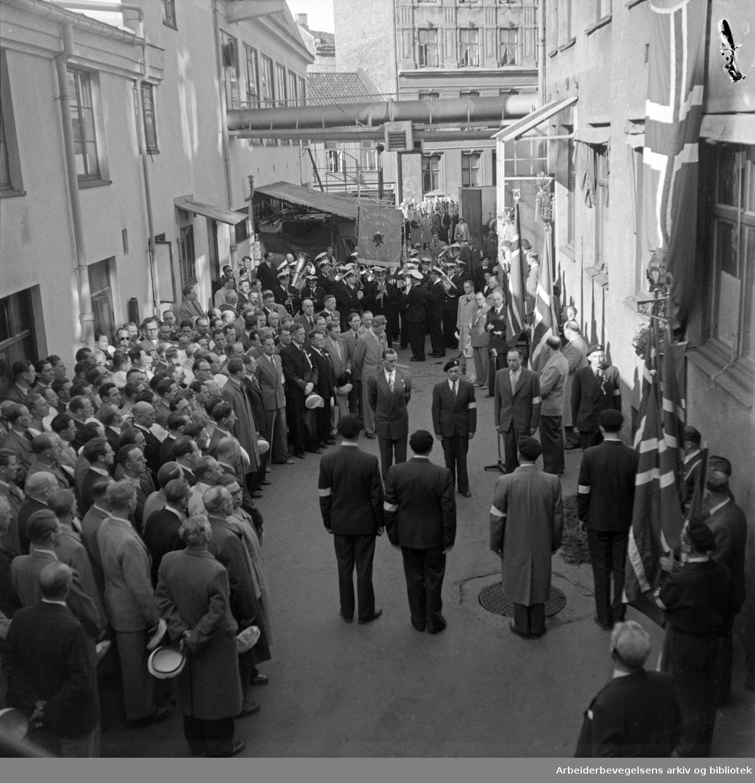 Minnehøytidelighet for falne arbeidere utenfor Emil Moestue A/S' trykkerier, Nordbygata 12 på Grønland. Bekransning av bedriftens minnetavle. Oslo Brannvesens Musikkorps. Nylandskoret. 17. mai 1951.