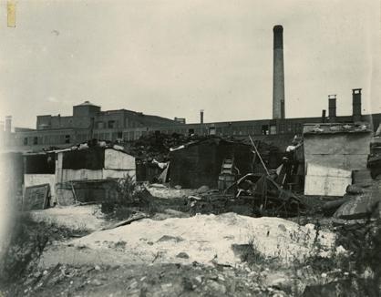 """Tre boligbrakker i """"Ørken Sur"""", Brooklyn NY, ca 1929-1935. En mann jobber på brakken til høyre i motivet. I bakgrunnen fabrikk med fabrikkpipe."""