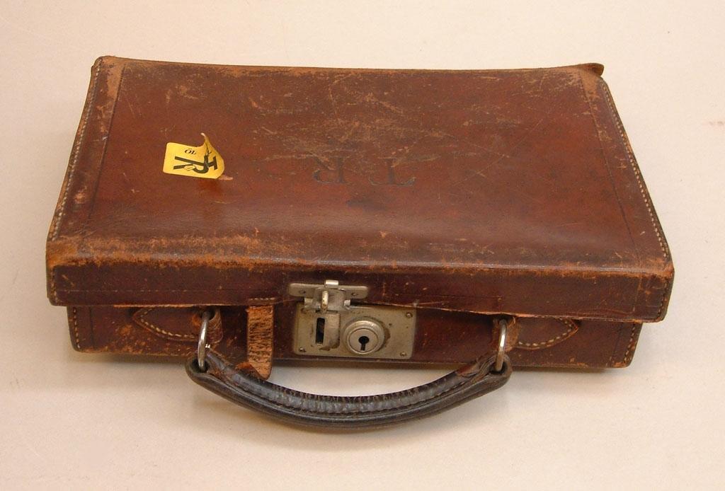 """Liten väska i brunt läder med TR-märkning stansat på locket. Handtag av dubbelsytt läder, ett lås ovanpå samt en rem att fästa locket med. Saknar dock nyckel. Gult klistermärke av nyare modell på framsidan: med TR-pojken och bokstäverna """"ÖL"""" på."""