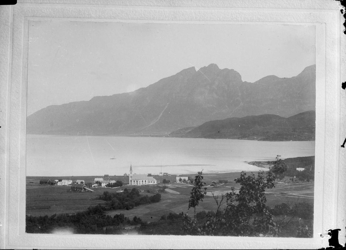 Repro. Landskap med fjell, fjord og med Ibestad kirke i front.
