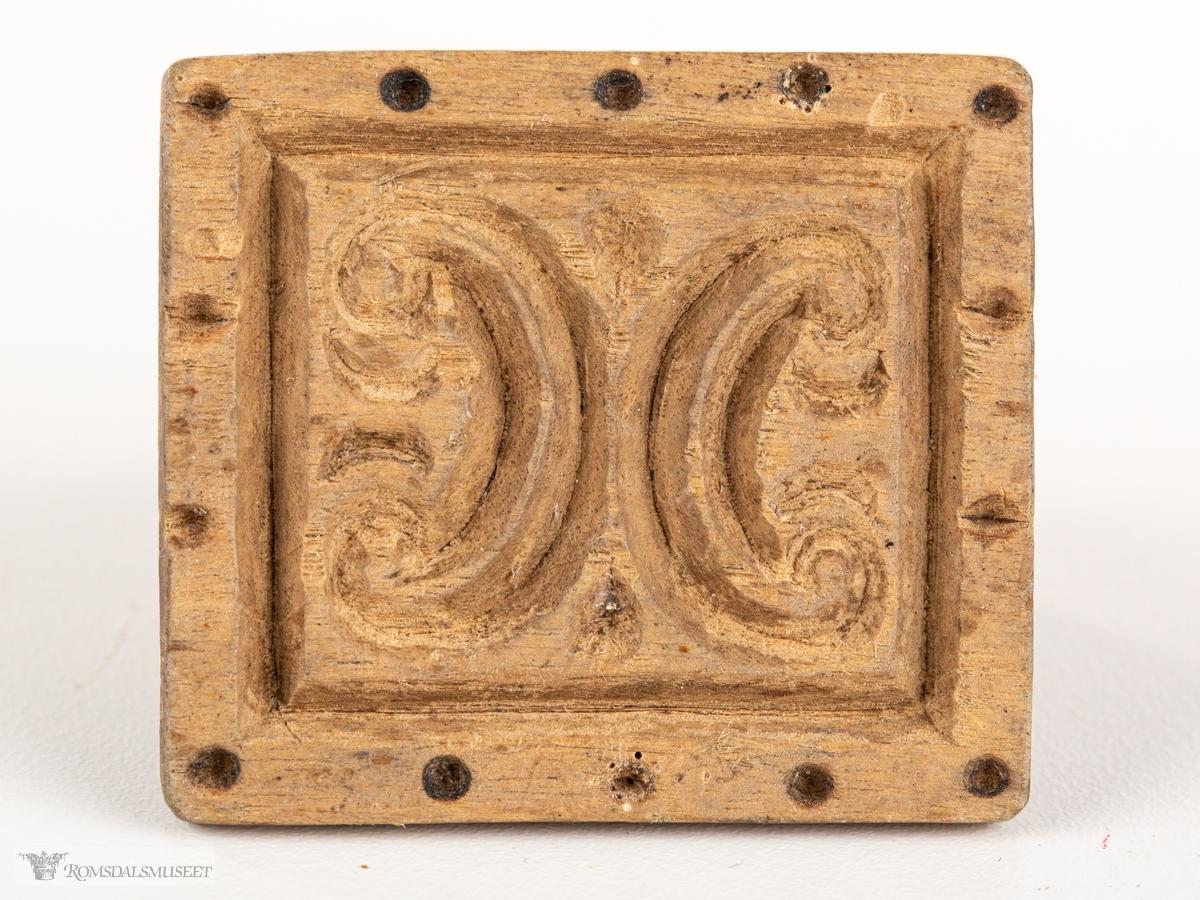 Mønstret har en rektangulær ramme med prikker langs randen. Inni er et symetrisk mønster av buer.