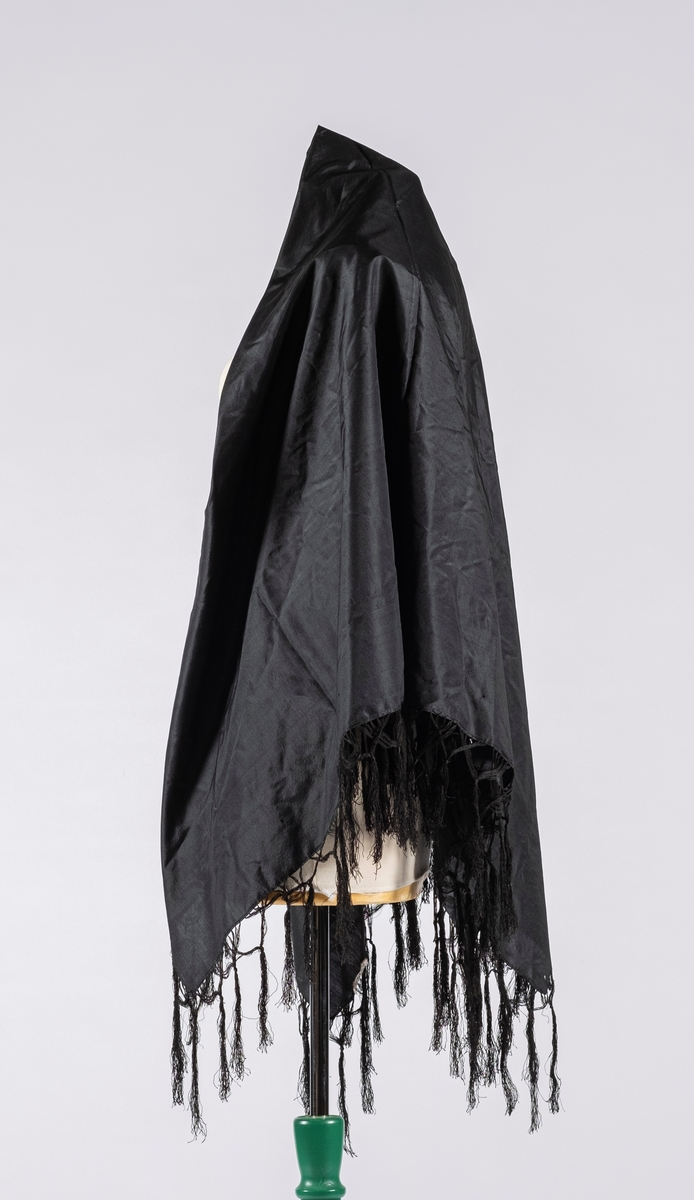 Firekantet svart sjal i taft med knyttet frynsekant. Klippekant i to av endene som er sydd inn.
