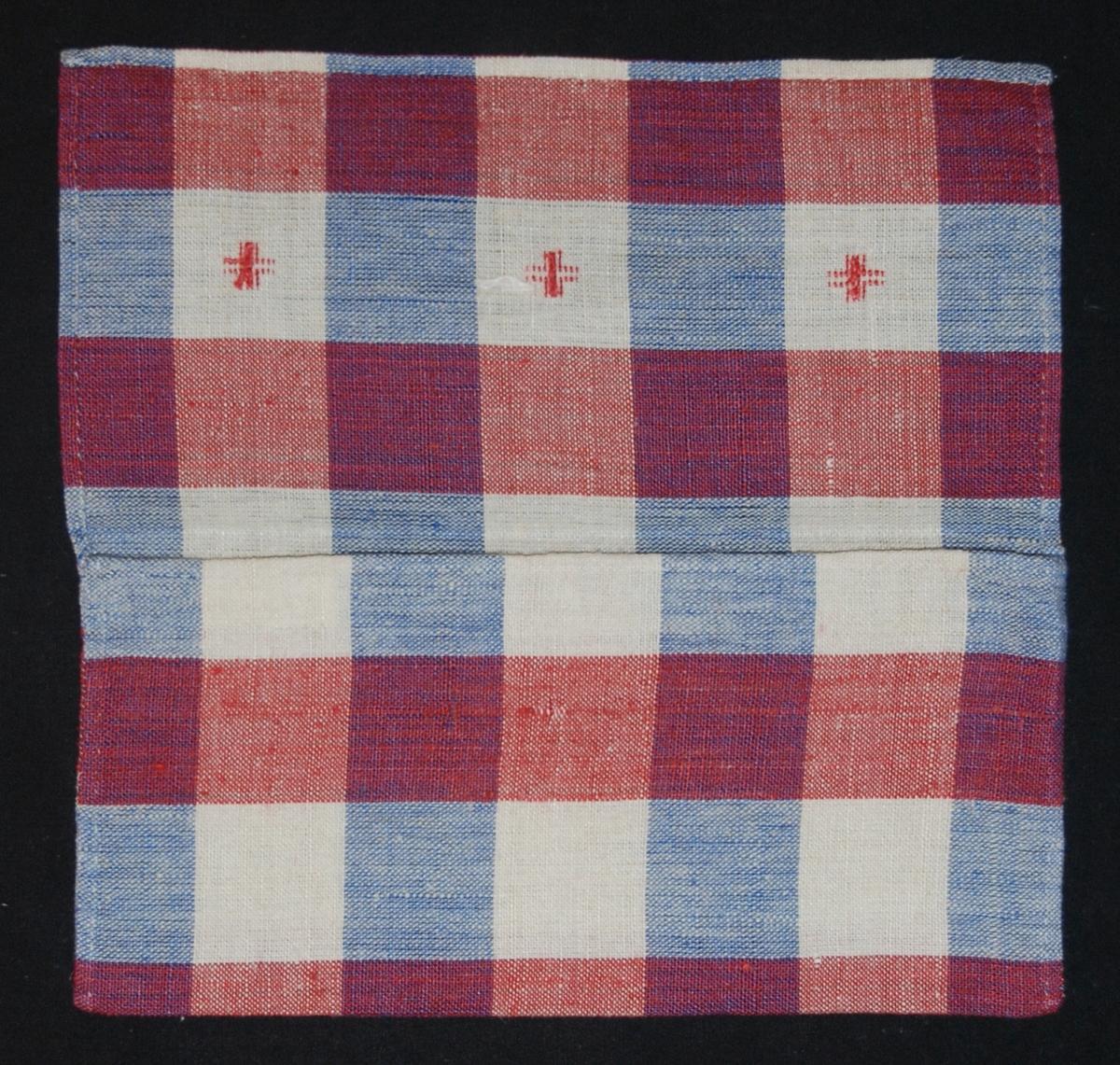 Handvävd linnelärft, rutig i vitt, blått och rött, kuvertmodell med övervikt lock, 3 kors broderade i korssöm med rött lingarn i de vita rutorna på locket.