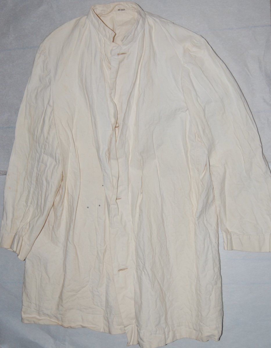 Ubleket lerret, åpning foran, isydde ermer, fem folder i nakken, smal halslinning, plastknapper. Håndsydd.