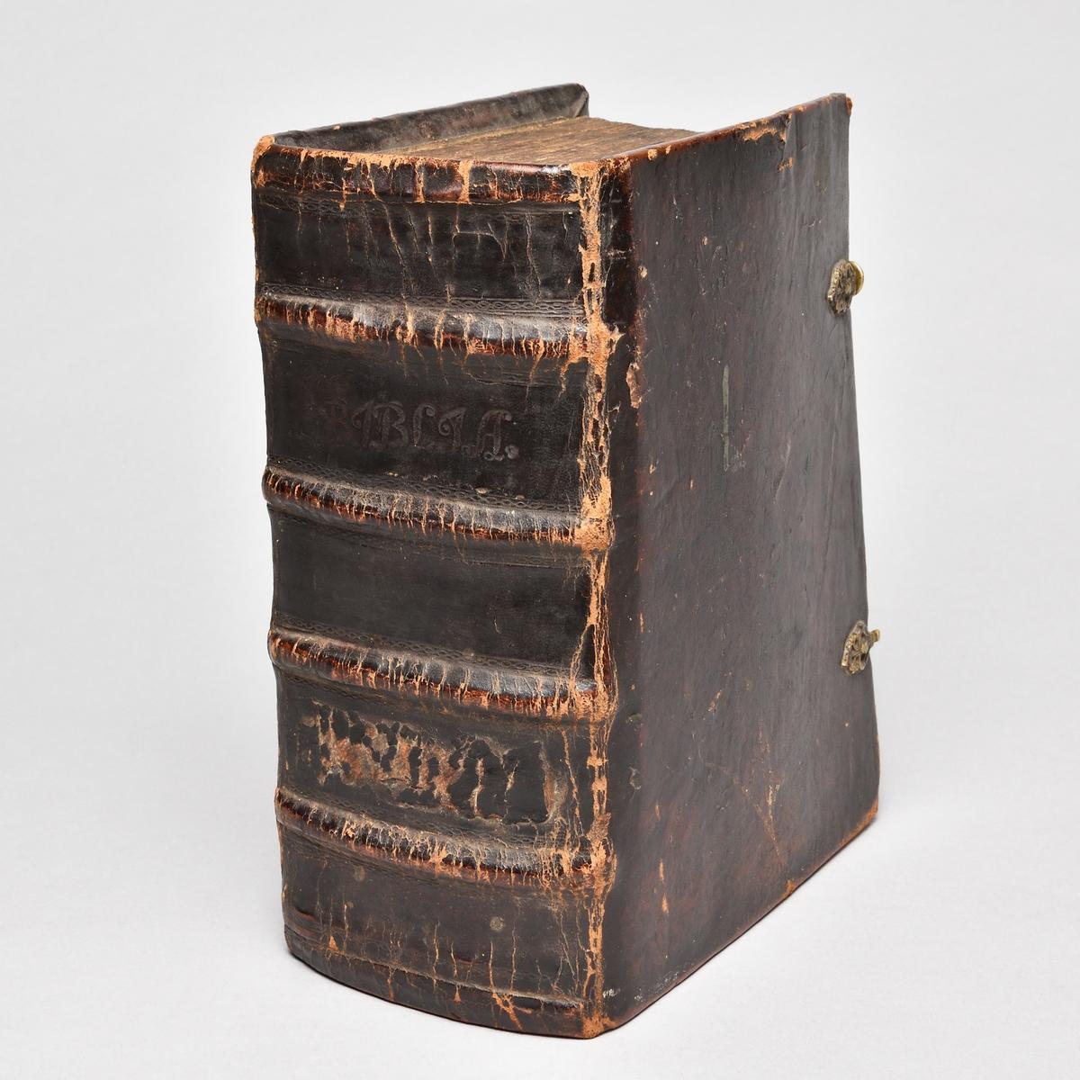 Bibel med band av skinn, rygg med fyra upphöjda bind. Två bokspännen av skinn och mässingsknäppen.