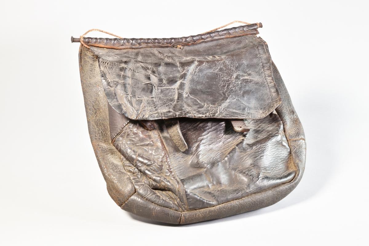 Jaktväska av svart läder med axelrem och lock, fyrsidig. Locket låses med två remmar samt spännen. Locket fastsatt runt en järnsprint som löper utmed väskans bredd. Axelremmen avbruten.