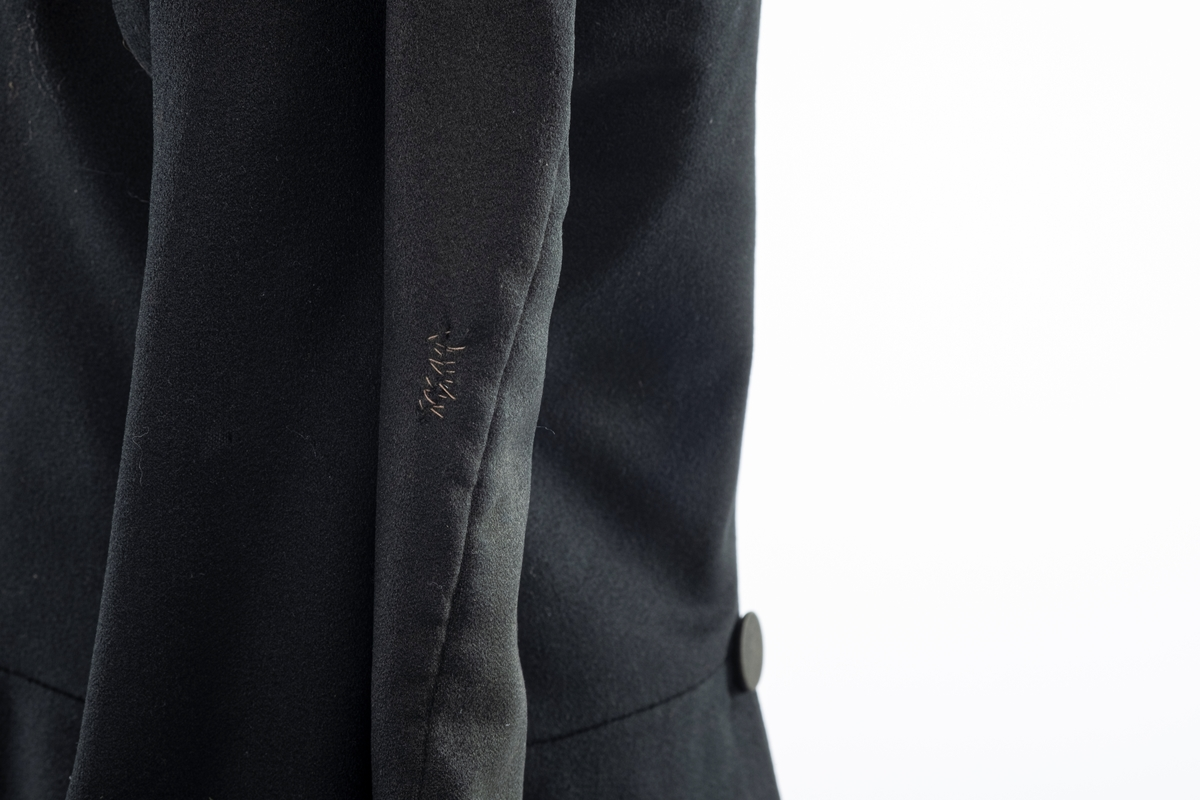 Svart jakke i ull med foring av bomull. Den har dobbelspent knepping og innsvinget liv. Knappene er trukket med tekstil.