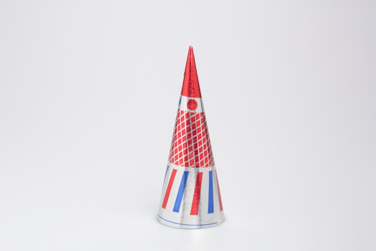 Kjegleformet iskrempapir (kremmerhus) i aluminium og papir. Kremmerhuset er med farger på utsiden, og uten farge (hvit) på innsiden. Kremmerhuset har sølv bakgrunnfarge med rødt felt nederst, rød rutete mønster i midten og blå og rød vertikale striper øverst.