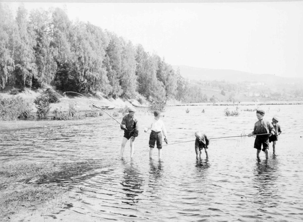 Repro: Fem gutter som vasser og fisker i vann.