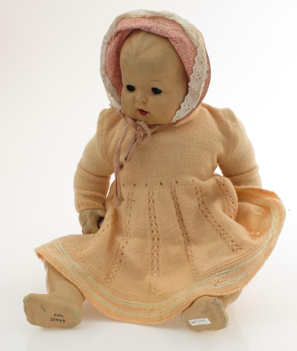 a) Sovedukke i babystørrelse. Tynn plastoverflate på mer solid base. Kropp, hode, armer og ben er leddet. Øyer har vært lukket i liggende stilling.  Ikledd rosa strikket kjole, strikket undertøy og kyse. Løst plagg følger med. b) Kjole strikket, rosa farge.  c) Underkjole d) Bukse e) Kyse  f) Bukse med seler (lå i kufferten)