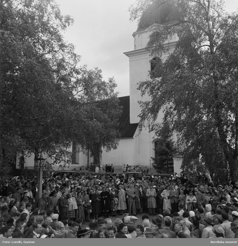 Motiv: (ingen anteckning) ; En folksamling vid Rättviks kyrka, en folksamling står vid en brygga när kvinnor och män går ombord på två kyrkbåtar.