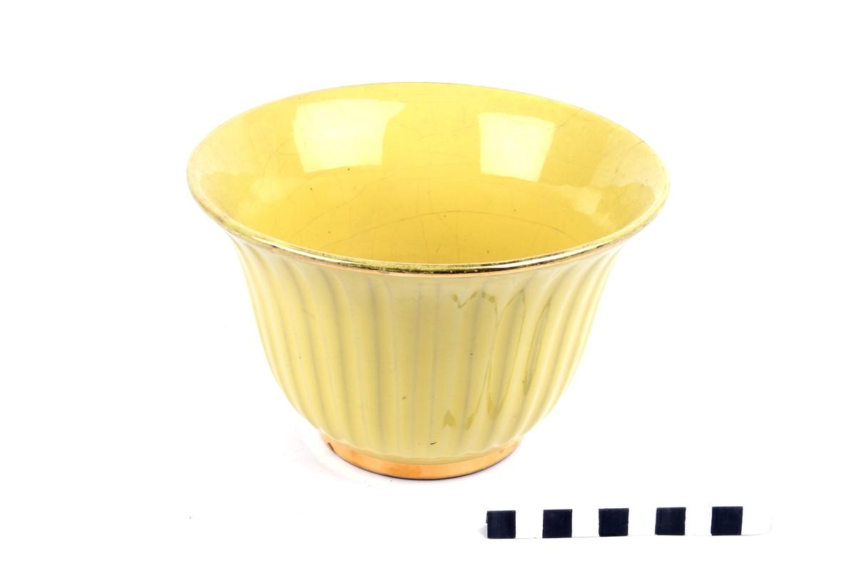 Blomsterpotte med rillet dekor og med gul, blank glasur og gullfarget kant.