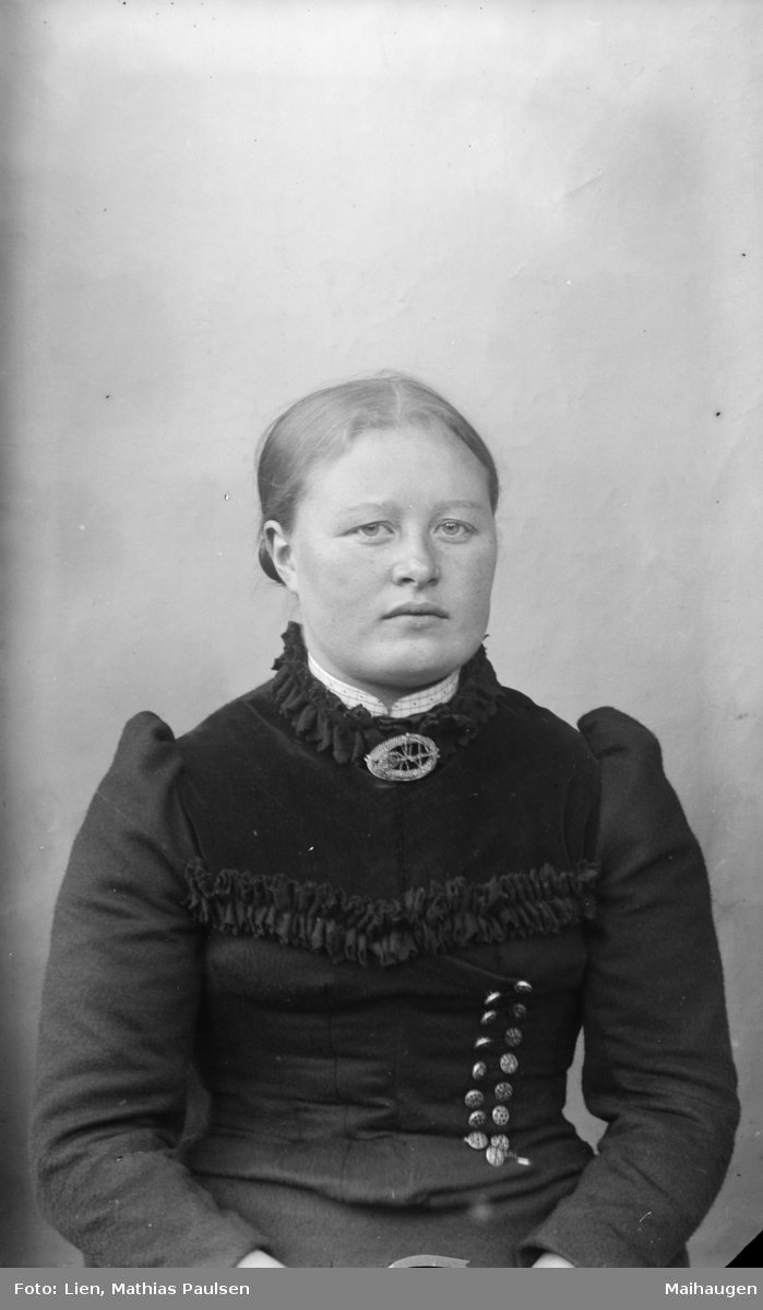 Portrett av kvinne med glatt hår med midtskill, kledd i mørk stakk og overdel med puffermer pyntet med dekorsøm og knapper
