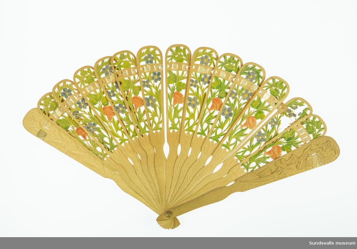 Tillverkad i ett ljust träslag med ett skuret, genombrutet blommotiv, vilket målats i grönt, blått, rött och gult.