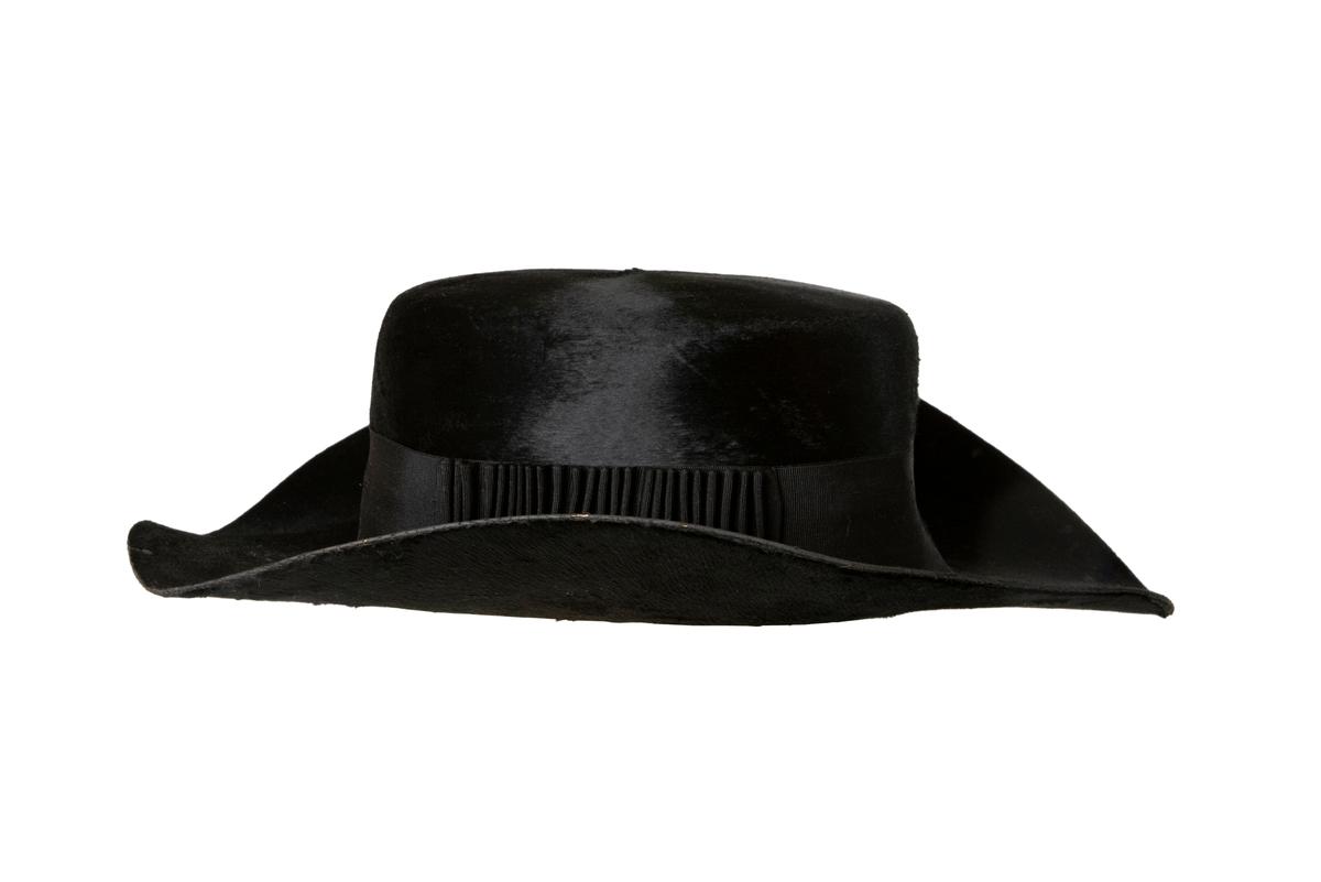 Hatt av svart silkesfelb, rund fesformad kulle, ganska vitt brätte. Svart sidenripsband runt kullen. Hatten är fodrad med rött och svart siden.