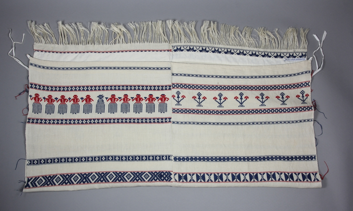 Hängkläde, handvävt, med linvarp och inslag i lin och bomull. Botten i tuskaft, plockade bårder i upphämta i rött och blått. Bårderna med dels rutmönster och stjärnor, dels djur, växter och människofigurer. Två våder hopsydda.  Kopierad efter en kopia från 1931 föreställande NM.0062086 hos Nordiska museet.