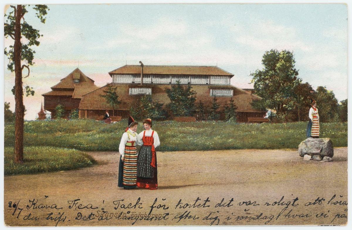 Vykort med motiv från Skansen. Tre folkdräktsklädda kvinnor utplacerade i miljön framför fågelhus (voljär) och Fatburen.