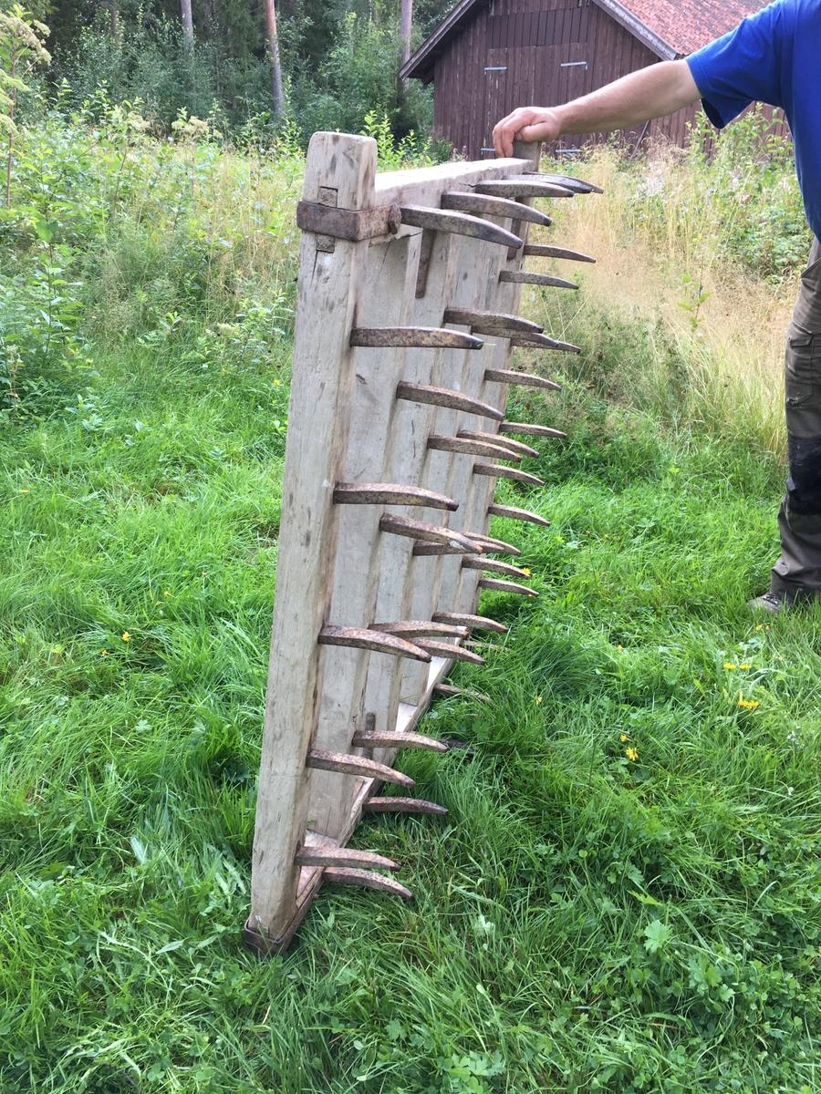 Harv med ramme av treverk (bjørk) og smidde kroker. Lokalt håndverk. Den er laget for nedmolding av korn og har spor av et diagonalt trekkpunkt. Jordbruksredskap til hest hovedsakelig brukt av menn.  Tilstand god