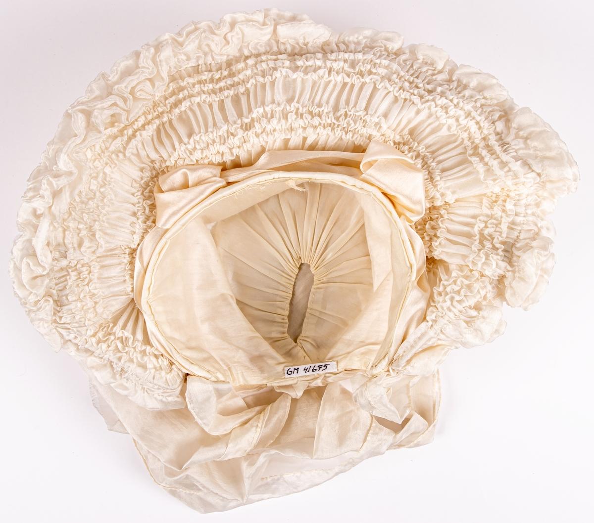 Hatten har långa vita band att knyta under hakan. Färgen är gräddvis. På var sida om kullen finns två tygblommor formade av sidentyg. Kullen är av ull, resten av siden.