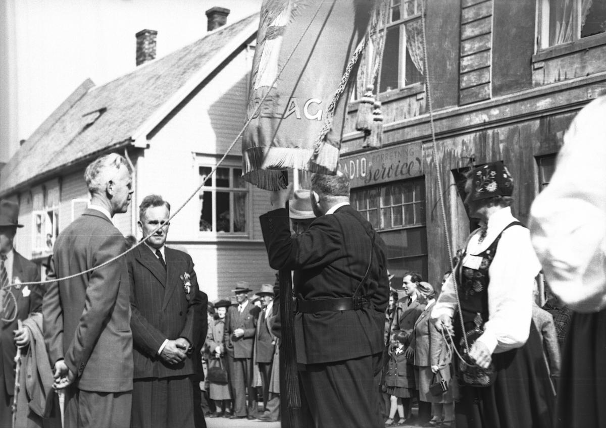 Opptog i Harstad. Mann med fanen til Norges Bondelag i midten.