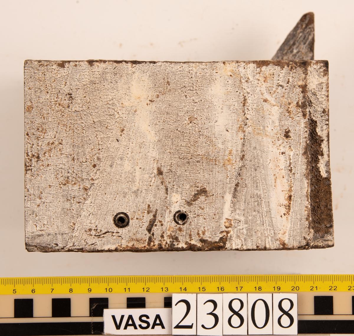 Del av bordläggningsplanka. Biten har 20 stycken hål efter borrprov, ytterligare 2 borrspår i hörnen och ett stort genomgående hål från tidigare dränering. Biten har en dymling i ena sidan.