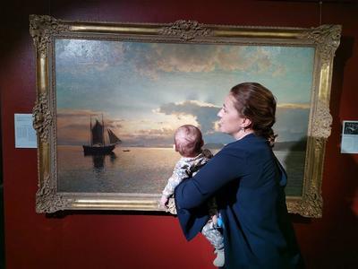 Kvinne med barn på armen står og ser på et maleri.. Foto/Photo