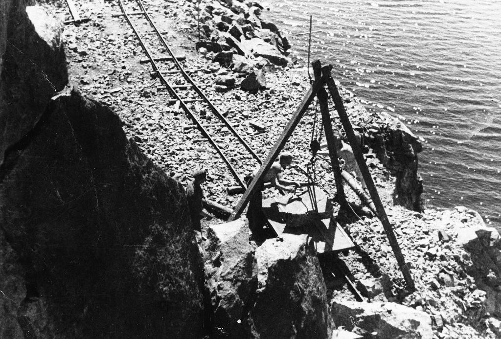Menn frå Arbeidstjenesten på vegarbeid ved Tveitavatnet i Bjerkreim. Her i arbeid med steinbukk. Sjå også: 1990.1TIM.25.013, 1990.1TIM.25.015, 1990.1TIM.25.016 og 1990.1TIM.25.017