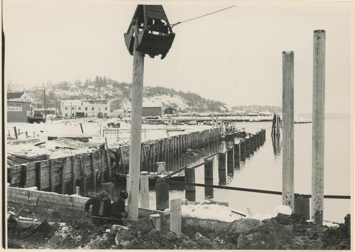 Værla. Kaianlegg. Vinter. 1967/1968.  Fotograf har stått ved Strandgata. Detaljer:Peledunking, arbeidere, bryggebygging, Gernerbrygga og Kleberget i bakgrunnen. Historikk: Bryggeområdet ble utvidet i en periode rundt 1968.