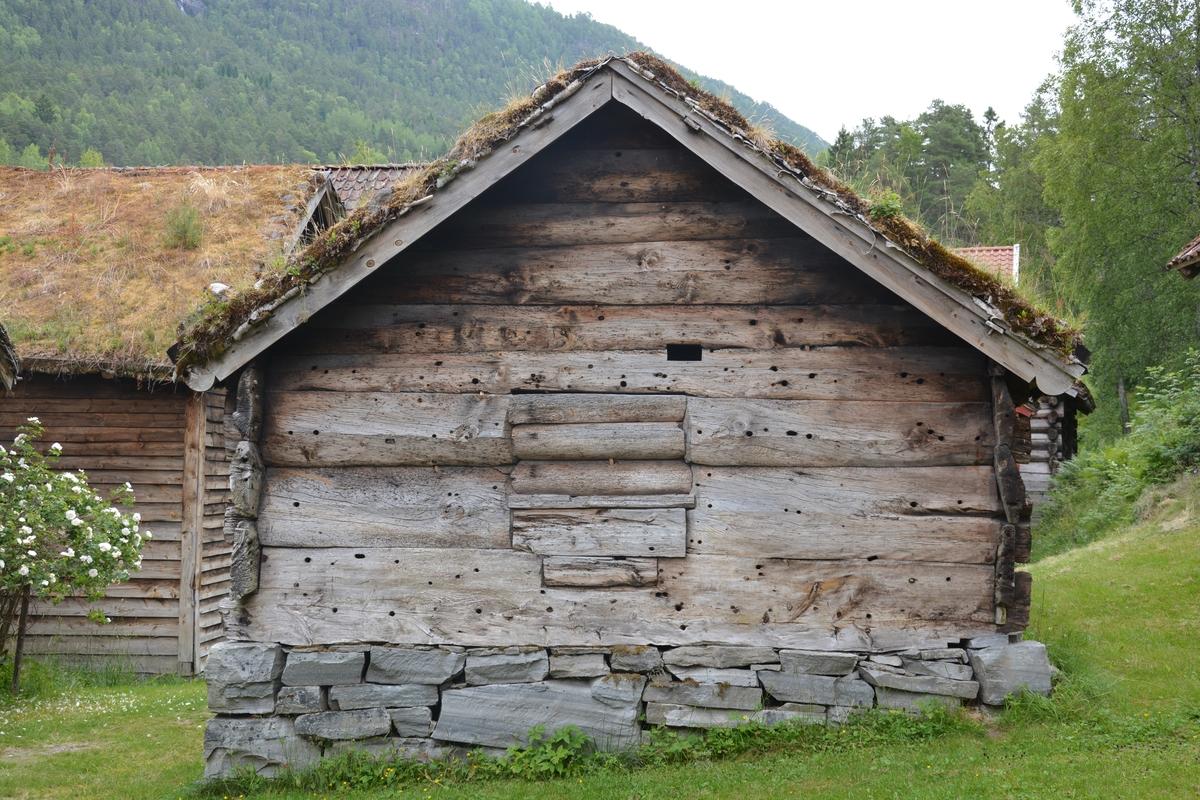 """Toromsstove: stoverom og """"dør"""" (gang) Lafta hovudrom. Stort tømmer er brukt, det er berre tre stokkelag opp til raftet. Stokkane er hogne smale med høgt tverrsnitt. På innsida er veggane slette, på utsida hr dei eit særmerkt prismeforma tverrsnitt. """"Døra"""" (gangen) er av reisverk. Det er mange navarhol på veggen utvendes. Gråstein tørrmur som underlag. Torvtak Stova er utan glas og med jordgolv. Spor / merke etter ei opning som (iflg.protokoll) skal ha vore ei likdør, som berre vart opna når nokon var død, til å føre ut liket. Elles var den alltid stengt for at ikkje attergangarar skulle finne vegen inn att.  Stova hadde steingrue i kråa til høgre for inngangsdøra (Omtalt i 1946, truleg ikkje sett opp igjen då museeet flytta til Jølet). Opphaveleg har stova nok hatt åre. Taket har tre sperrepar. Ljorekassa er mellom dei to sperrepara næraste døra. Ved deb eine langveggen er det no ein veggfast benk. Det er spor etter ein slik på andre langveggen og, og på den indre gavlveggen. Spora er gjennomgåande flate hol, truleg til knektar som har bore benkeplata. Opningane i stova er midt i begge gavlveggane, døra i den eine og ein attbolking i den andre. Døra har den alderdomlege beitskiforma med grop i beitskia for veggtømmeret (ikkje grop i tømmeret). Dørstokken er gjennomhoggen, truleg etter hogging av kjøt. Den andre opninga går over 1 1/2 stokkebreidd, ca 90 x 60 cm. Denne er omtala som """"likluke"""".  Rommet framfor, """"døra"""" har berre einfelde tynne bordveggar. Huset har mange gamle trekk, men det er ikkje nok haldepunkt for datering. Laftehals med garpe midt i stokken er kjend frå mellomalderen, og den høgstrekte forma på halsen vart t.d. nytta gjennom heile 1700-talet."""
