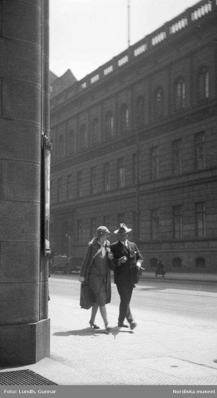 """Motiv: Utlandet, Berlin 114 - 146 ; Gatuvy med en kvinna och en man som går på en gata, anteckningar på kontaktkarta 139 """"Monument vid Riksdagen, Berlin"""" 140 """"Monument vid Siegessäule""""."""