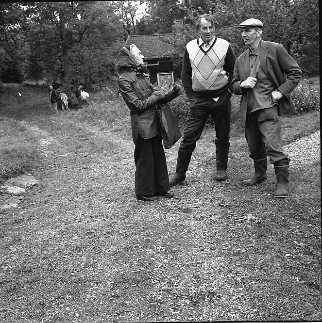 Tre okända personer, en kvinna och två män, står vid en mindre grus/gräsväg.