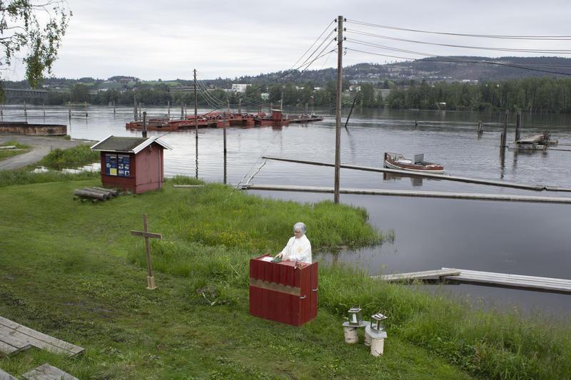 Prest ved alter med elva og fløtingsanlegget i bakgrunnen. (Foto/Photo)