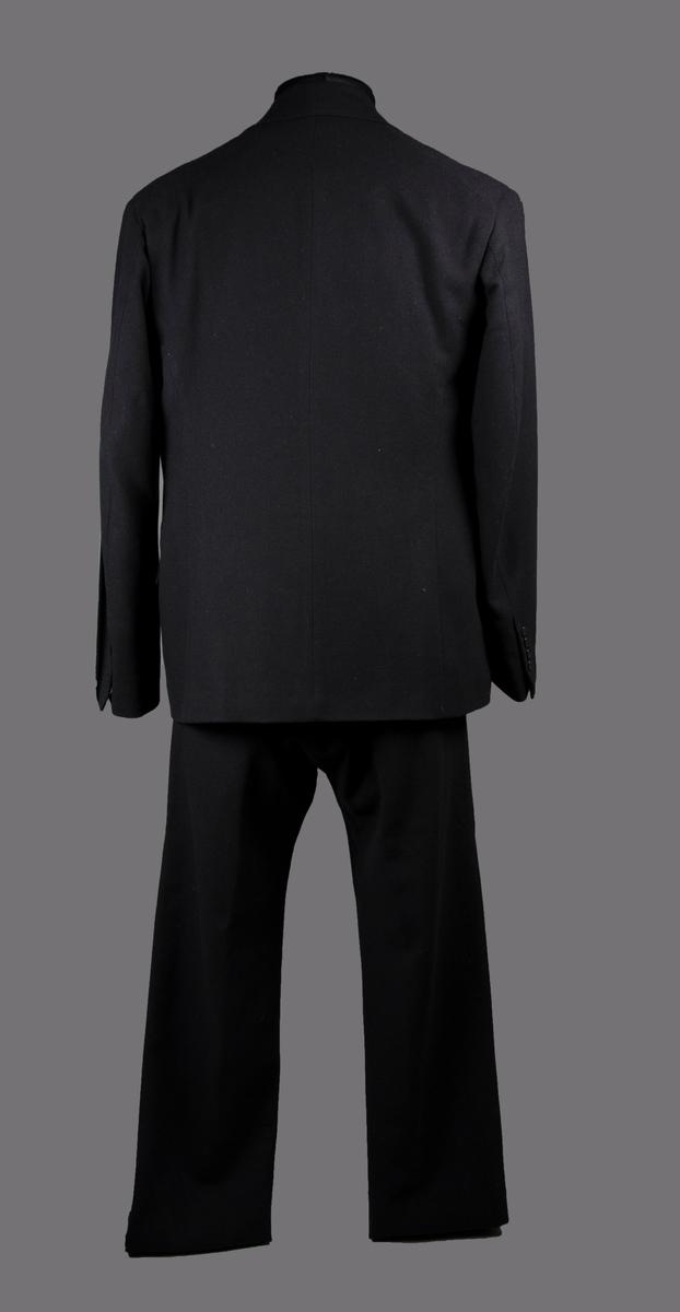 Tredelad svart yllekostym. En kavaj, en väst och två par byxor. Plaggen är alla sydda med klassiska skrädderimetoder som innebär underarbete och handsömnad.