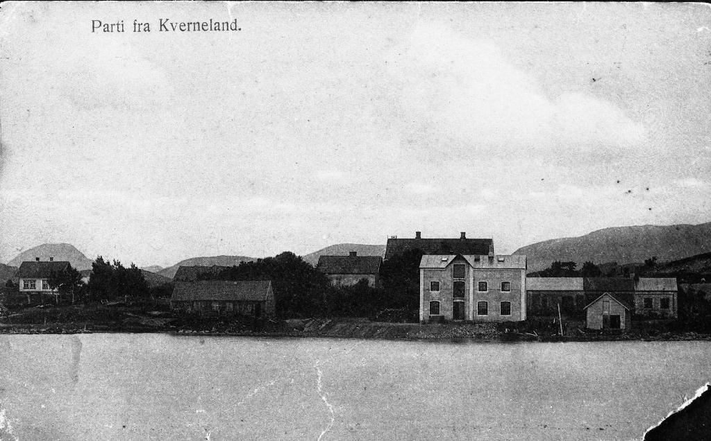 """Kvernelands fabrikk ved Frøylandsvatnet. Til v. """"Smia"""" som nå er flytt og er ein del av Museèt på Kvernaland. """"Smia"""" var der det starta og byrjinga på Kvernelands fabrikk. Så kjem """"Gubbahuset"""" og """"Storhuset"""" (ein kan sjå taket). Framfor står nytt fabrikkbygg. Ein del av dei står enno (1990) etter vidare utbygging."""