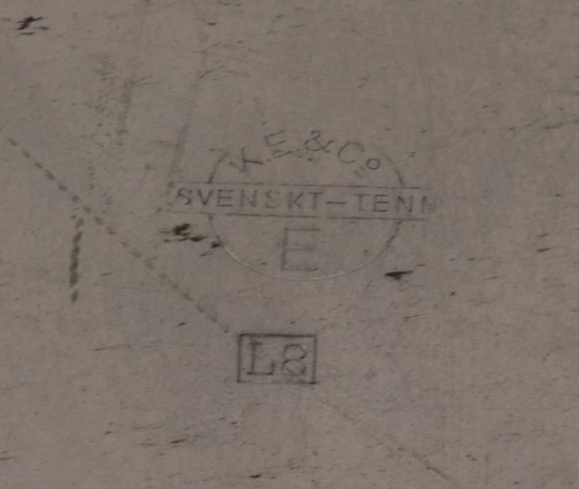 Minnestallrik av tenn med graverat motiv av Kiruna järnvägsstation i mitten. Motivet har en rektangulär ram. Tallriken har ett brett bräm indelat i flikar med en blomma i relief på varannan flik. Upphängningsögla fastlödd på baksidan.