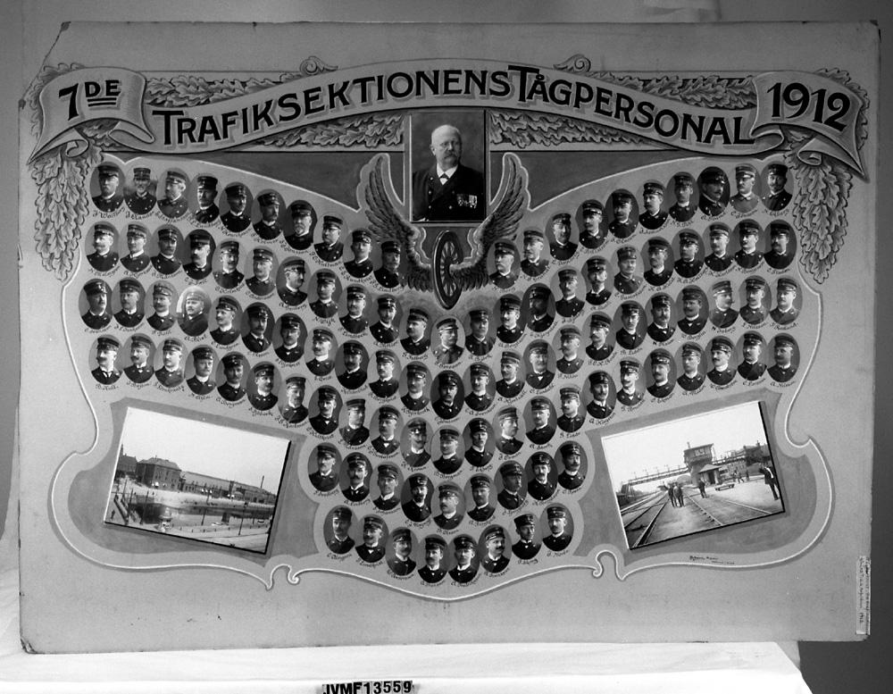 """Tavla med porträttsamling eller kollage, utan ram. Porträtten är ovala, och visar personalen vid SJ:s 7:de  Trafiksektion 1912. Text: """"7de Trafiksektionens Tågpersonal 1912""""  Gåva till trafikinspektor G G Arfvidsson, 1912"""