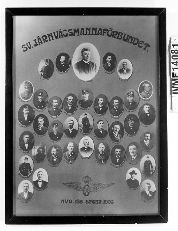 Tavla med porträttsamling eller kollage, i glasad svart träram. Porträtten är ovala, och visar de järnvägsanställda vid Mora-Wänerns Järnväg som var närvarande vid bildandet 1906-02-08 av Svenska Järnvägsmannaförbundet Avd. 135 i Vansbro.