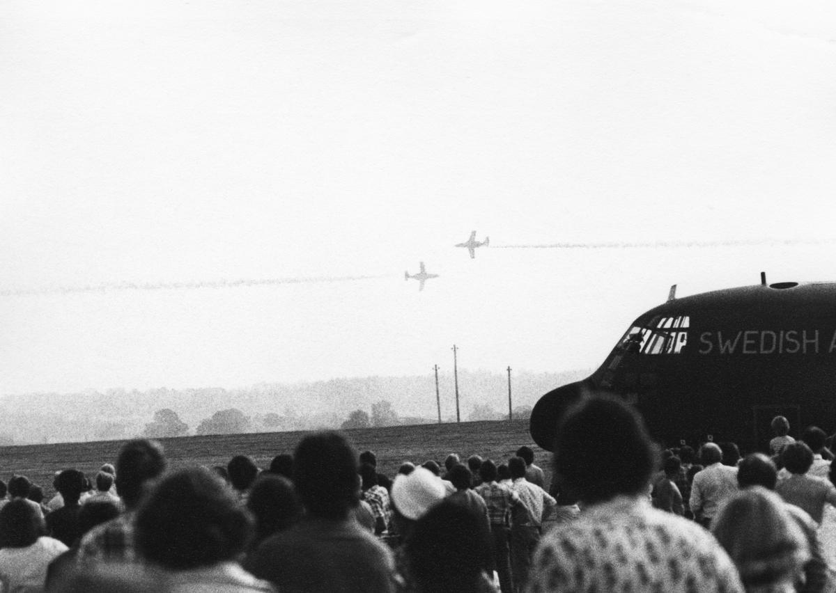 Avancerad flygning med två flygplan SK 60 ur Flygvapnets uppvisningsgrupp vid flygdagen på Malmen den 28 augusti 1976. Vid firande av Flygvapnet 50 år. Flygplanen syns på långt håll. I förgrunden syns publik samt del av flygplan TP Hercules.