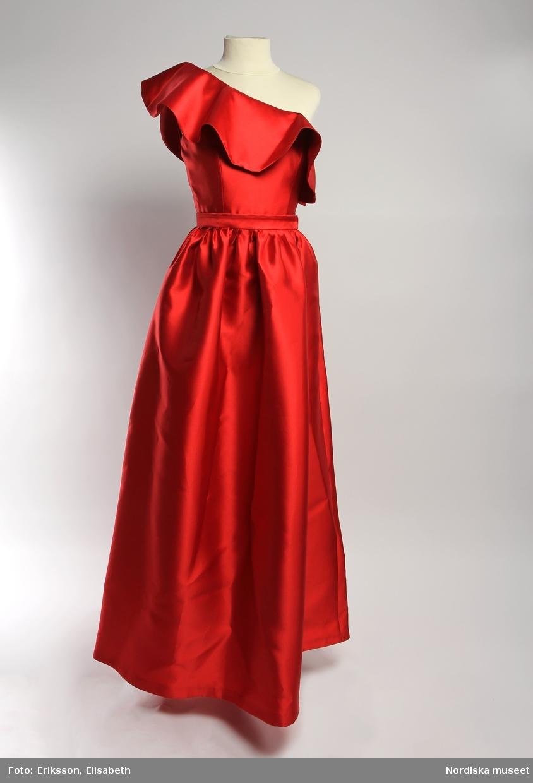 a. Klänning, lång, av rött glansigt tyg med fall. Ärmlös, oregelbundet skuren så den vänstra axeln bärs bar, överhängande 17 cm bred övre kantvåd, vågformig, ett smalt konstsilkeband för vänster axel/galge fästat på klänningens insida. Liv och kantvåd i dubbelt tyg, klänningen har rynkad kjol mot liv, dragkedja i vänster sida. Etikett BY MYLINA på insidan av ryggstycket. b. Slätt skärp av samma röda tyg som klänningens. /Helena Lindroth 2019-06-03