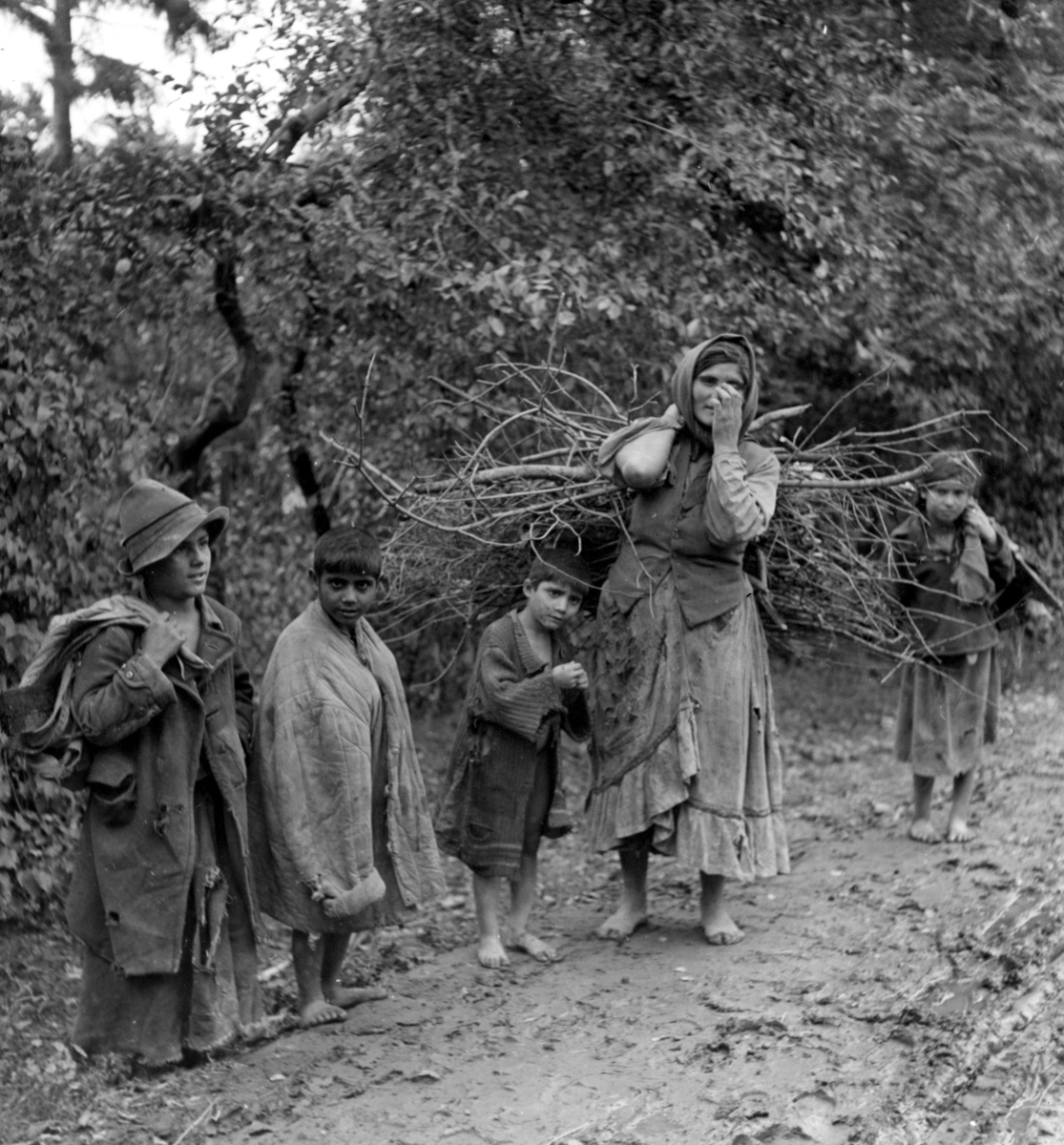 En romsk kvinna står vid vägkanten tillsammans med några barn. På ryggen bär hon ved hon samlat. Toleransen för romer har historiskt varierat mycket mellan olika samhällen, men romers närvaro har sällan setts som något positivt. Ofta fick man slå sig ned i läger samhällets utkant, man har förvägrats fast bostad och fördrivits. Boendestandarden bland svenska romer var under 1900-talets första hälft mycket varierande. Familjer som hade det bättre ställt kunde äga flera tält, medan fattigare familjer enbart hade ett tält. Man sov då där marken var minst lerig.