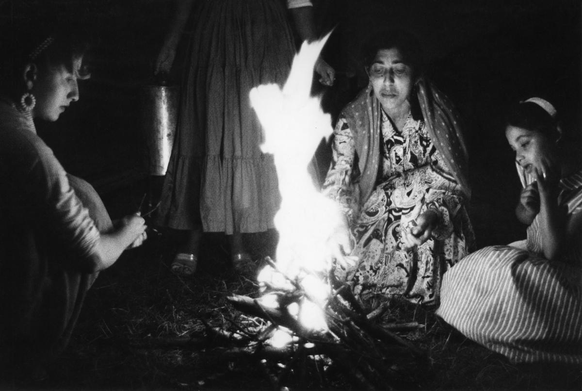 """En grupp romska kvinnor i olika åldrar sitter kring en brasa. Bilden är troligen tagen i samband med inspelningen av TV-programmet """"Du svarte zigenare"""", ett program av Victor Lindgren. Programmet sändes första gången 1960-08-30."""