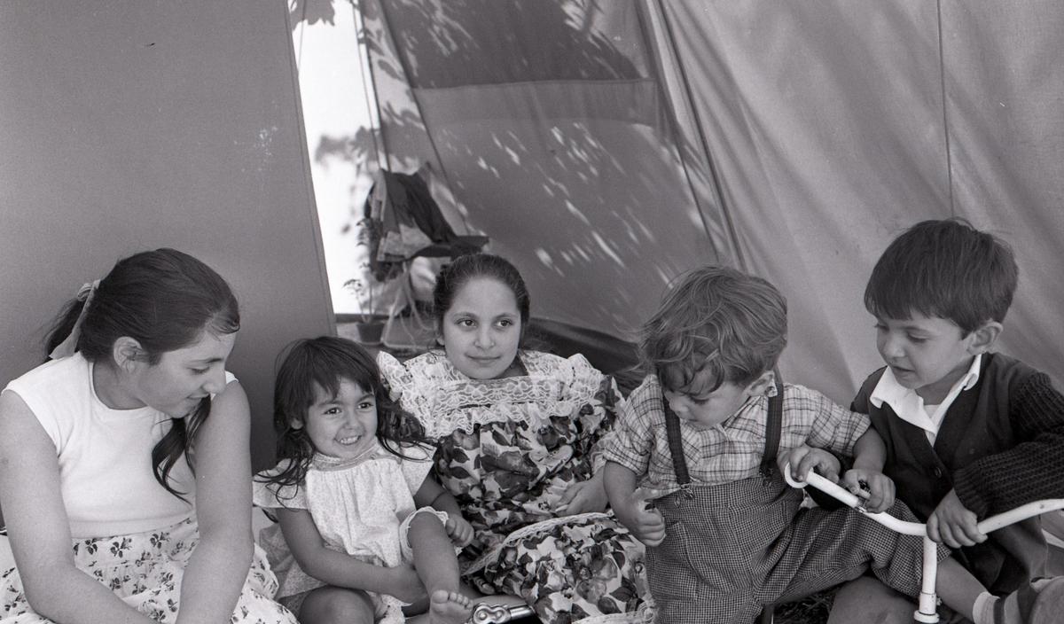 Några romska barn poserar framför kameran i Malmö sommaren år 1963. Bilden är tagen i samband med ett nyhetsreportage för Skånska Dagbladet. I reportaget porträtteras en romsk familj och hur de trivs med att ha blivit bofasta. Toleransen för romer har historiskt varierat mycket mellan olika samhällen, men romers närvaro har sällan setts som något positivt. Ofta fick man slå sig ned i samhällets utkant, man har förvägrats fast bostad och fördrivits. Hur ofta man fick stanna på en plats var olika från kommun till kommun, men sällan längre än tre veckor. Efter att de svenska romerna i Sverige erkändes som medborgare år 1952 uppstod debatt kring gruppens svåra levnadsförhållanden. En statlig utredning genomfördes under 1954-1956 där en av slutsatserna blev att fast bostad var nyckeln till att lyckas med skolgång och arbetsliv. Från och med mars 1960 hade kommuner möjlighet att rekvirera statsbidrag för kostnader i samband med romers bosättning, vilket förenklade möjligheten för svenska romer att få tillgång till permanenta bostäder samt i förlängningen studier och arbete. Denna process kom dock att bli utdragen under flera år.