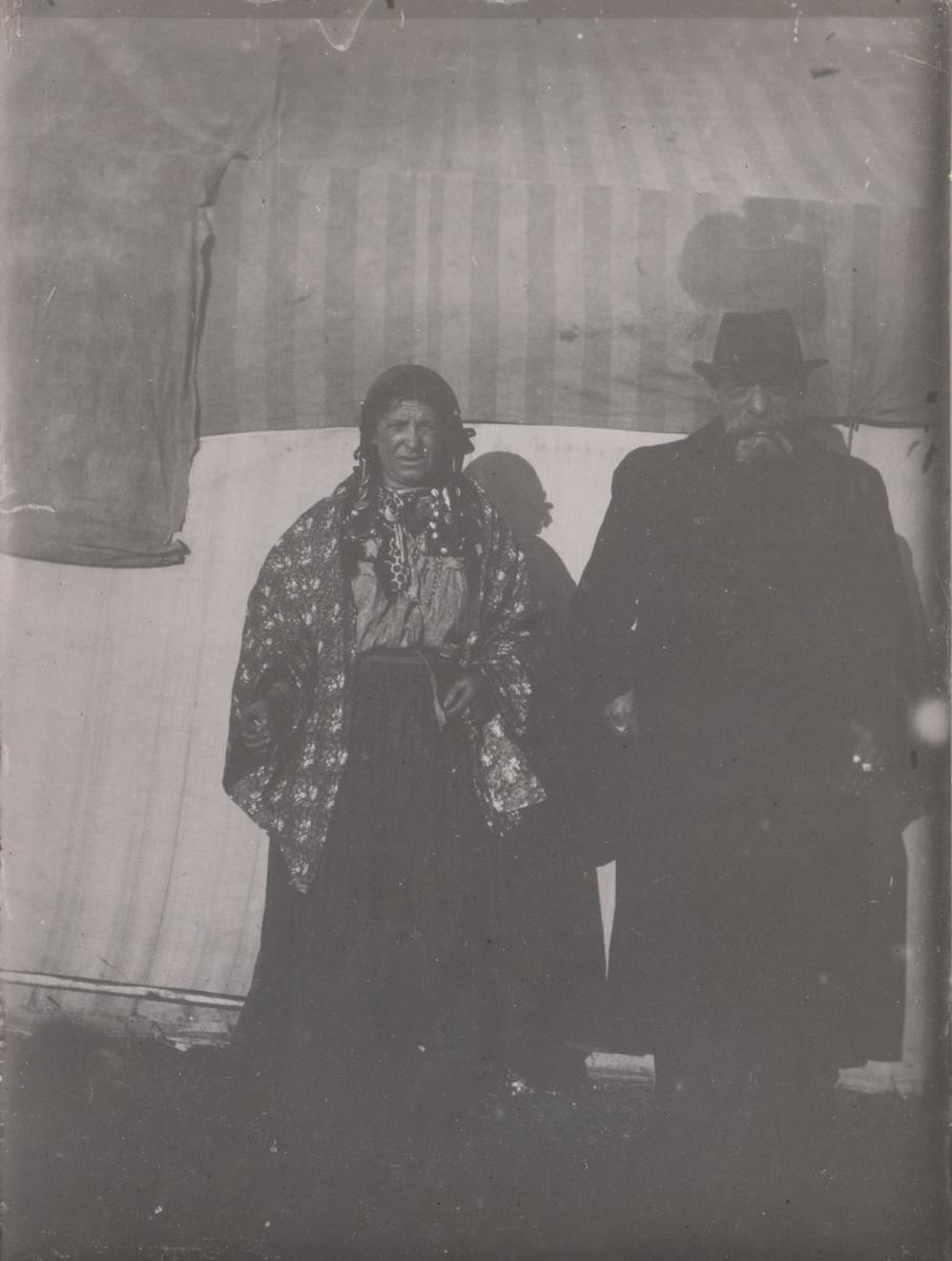 En man och en kvinna står framför vad som troligen är ett bostadstält. De tillhör troligen den grupp romer som folkvandrar genom Europa under 1800-talets andra hälft. Vid 1800-talets slut började romer från Sydeuropa i högre grad att resa runt i hela Europa för att idka handel och arbeta med hantverk. På 1860-talet avskaffades slaveriet av romer i Valakiet (ung. dagens Rumänien och Moldavien). De förslavade romerna talade valakisk romani, främst lovari, kelderash och tjurari. Efter slaveriets avskaffande sökte sig många av de befriade till resten av Europa, men även till Amerika, Asien och Australien. Denna folkvandring sägs ha pågått fram till första världskriget. I Sverige kom den dock att begränsas till följd av inreseförbudet för romer som infördes år 1914. Efter ankomsten av valakiska romer till Sverige börjar majoritetssamhället göra skillnad på skandoromer och valakiska romer.