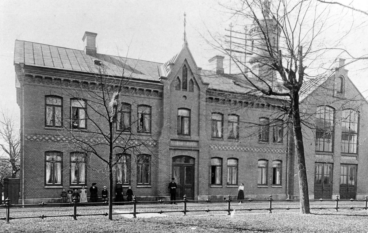 Brandstationen i kvarter Kristina. Fotot taget innan 1920 då portarna breddades. En man, tre kvinnor och sex barn står utanför byggnaden.