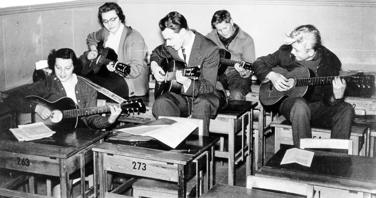 Kursverksamhet: Lindholms gitarrkurs. Fem personer sitter vid och på skolbänkar med varsin gitarr.