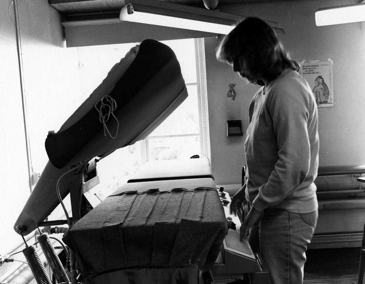 En kvinna jobbar med pressning av byxor och kjolar. Byxavdelningen, Drabant AB:s tredje våning.