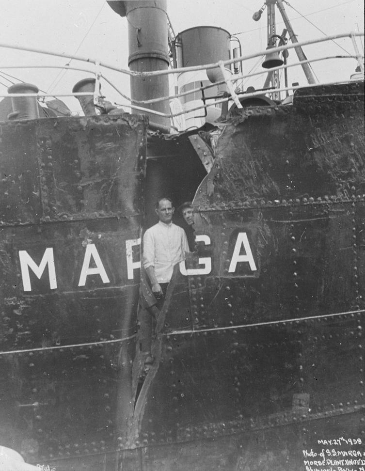 Dampskipet MARGA, to menn kikker ut gjennom revne i langsiden.