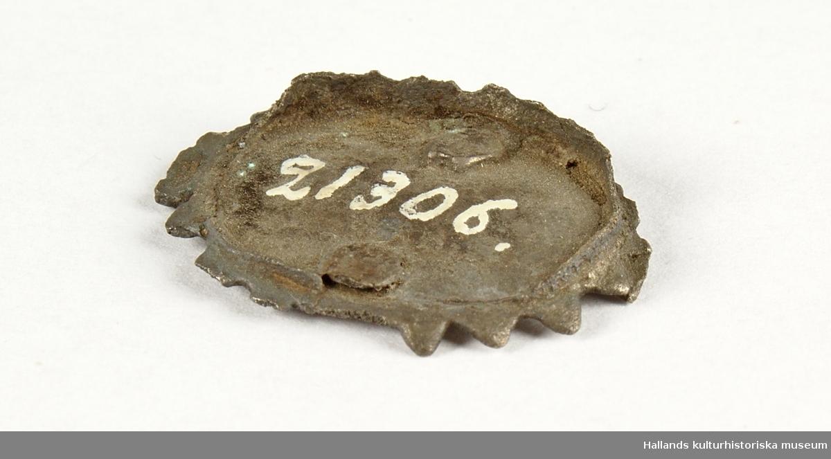 Ovalt smycke i silver med infattning för sten. Stenen är dock borta. Kanterna runt smycket är kantade.