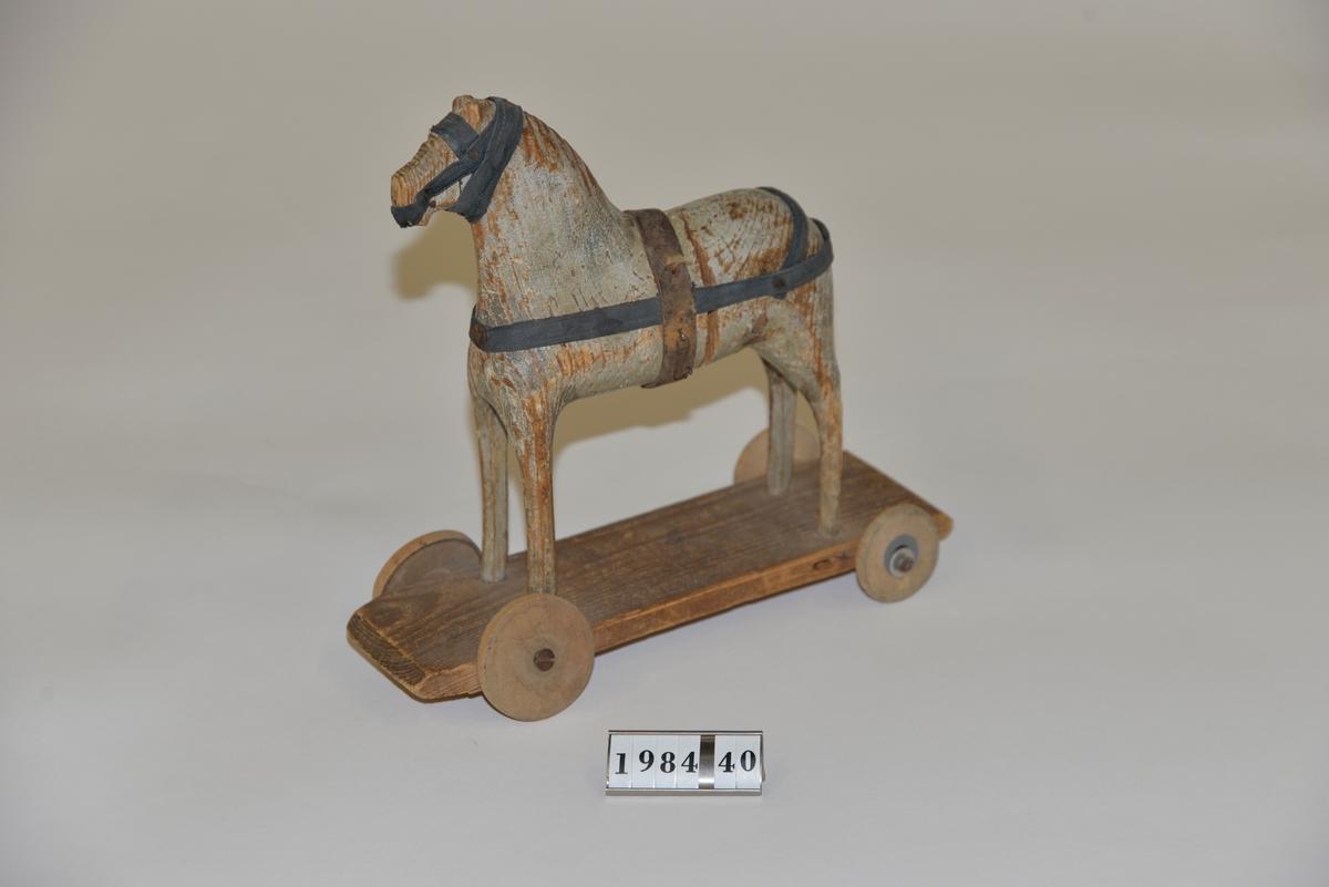 Leksakshästen är monterad på en platta med 4 st hjul. Grå-blå, mycket avskavd färg. Seldon av tyg och läder. Måttangivelserna avser plattan. Ägaren föddes 19200406