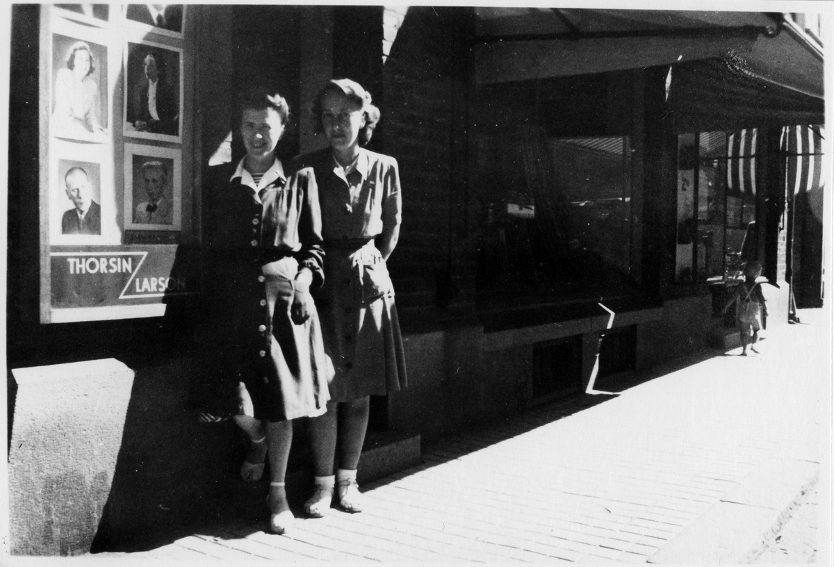 Två unga kvinnor i klänning som står utanför Thorsin-Larsons fotoateljé.